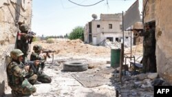 A handout picture released by the Syrian Arab News Agency (SANA) shows a unit of the Syrian armed forces taking position during a patrol near Al-Manashir roundabout in Jobar in the outskirts of Damascus on July 14, 2013. According to SANA, the unit allege